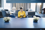 Mid adult businesswoman reading book in office lobby - MASF02288
