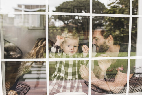 Mid adult man with daughters seen through window of home - MASF02297
