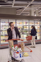 Mature man talking on mobile phone while woman looking at display cabinet in refrigerated section of supermarket - MASF02303