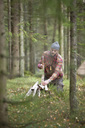 Mid adult man cutting firewood with axe in woodland - MASF02309