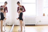 Smiling teacher talking to girl in ballet studio - CAVF36096