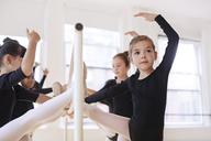 Confident ballerinas leaning on rod at studio - CAVF36105