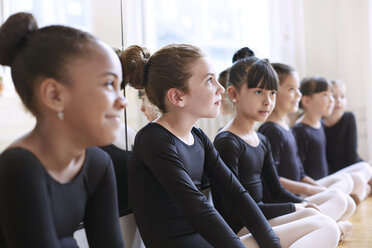 Thoughtful ballerina sitting with friends at ballet studio - CAVF36114
