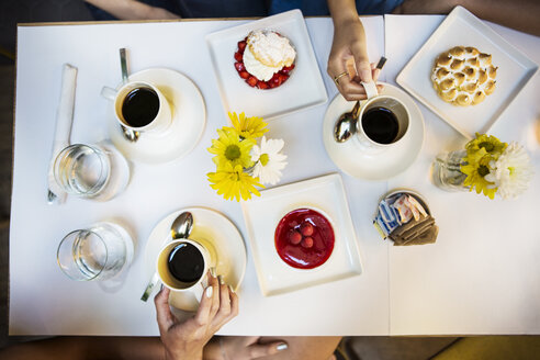 Cropped image of friends having coffee and dessert at table in restaurant - CAVF36204