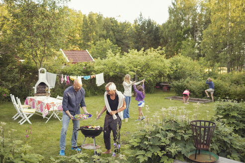 Man and woman cooking vegetables on barbecue grill with kids enjoying garden party - MASF02313