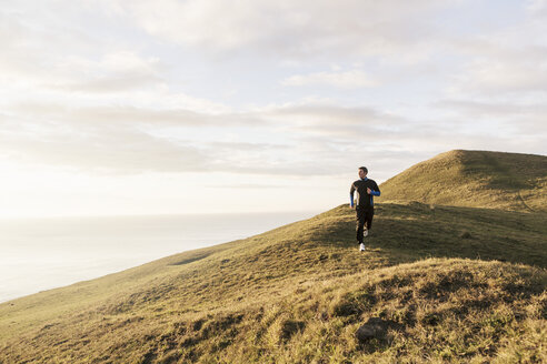 Man jogging on hill by sea during sunny day - MASF02325