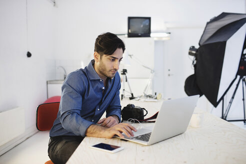 Male blogger using laptop at desk in creative office - MASF02328