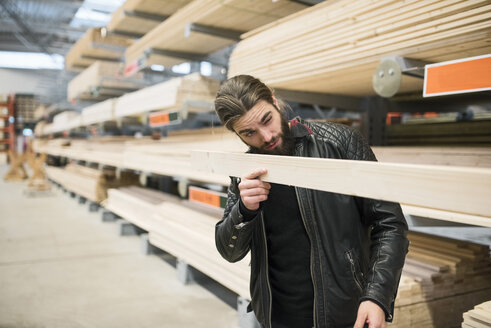 Male customer examining wooden plank in hardware store - MASF02334
