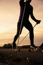 Low angle view of mature man roller skiing on road against sky during sunset - MASF02337