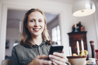 Low angle portrait of young woman using mobile phone at home - MASF02355