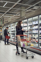 Man and woman buying food from refrigerated section at supermarket - MASF02361