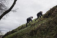 Low angle view of multi-ethnic couple climbing on hill in forest - MASF02367