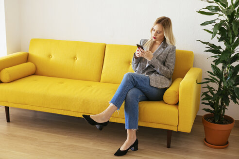 Businesswoman sitting on yellow couch, using smartphone - EBSF02337
