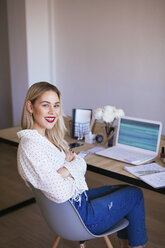 Blond businesswoman sitting at desk, working - EBSF02358
