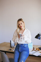 Young woman working in office, taking a break, drinking coffee - EBSF02364