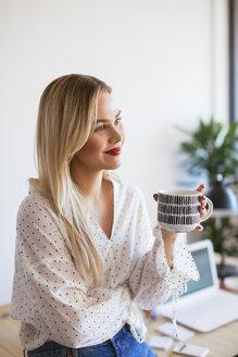 Young woman working in office, taking a break, drinking coffee - EBSF02367