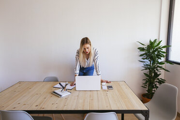 Young businesswoman standing at desk, using laptop - EBSF02382