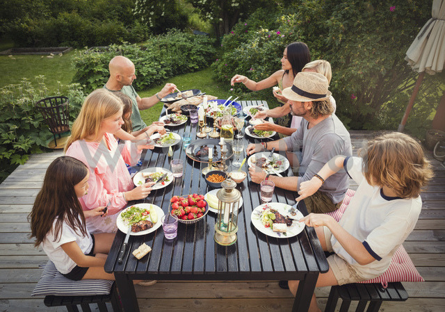 High angle view of family and friends eating lunch in back yard - MASF02373