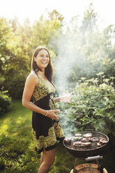 Happy woman standing by barbecue in back yard - MASF02376