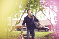 Happy man carrying luggage on steps at back yard - MASF02388