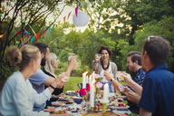 Happy friends toasting glasses at table in garden party - MASF02391