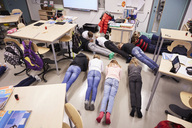 High angle view of junior high students in plank position at classroom - MASF02406