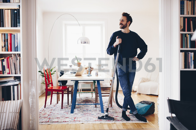 Happy man standing with vacuum cleaner in dining room at home - MASF02415 - Maskot ./Westend61