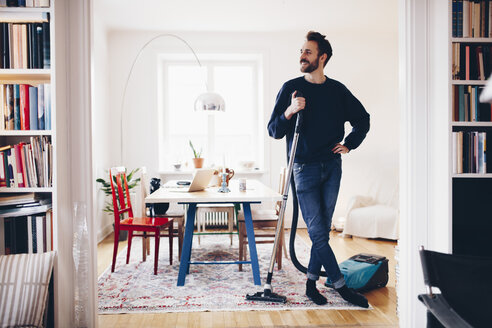 Happy man standing with vacuum cleaner in dining room at home - MASF02415