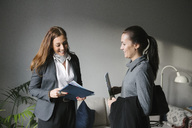 Happy woman and female realtor discussing brochure at home - MASF02418
