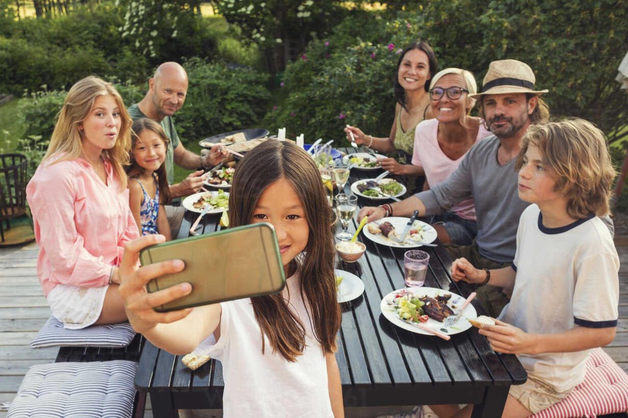 Happy family and friends looking while girl taking selfie from mobile phone at back yard during garden party - MASF02427 - Maskot ./Westend61