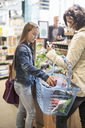 Girl putting pomegranate in basket carried by mother at supermarket - MASF02439