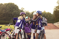 Girls showing mobile phone to friends standing with bicycles on footpath against sky - MASF02448