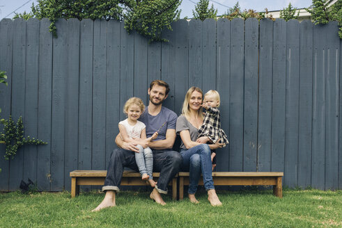 Full length portrait of happy parents and children sitting on seats against fence at yard - MASF02451