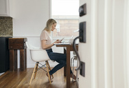 Full length side view of mid adult woman holding mobile phone while using laptop at home - MASF02454
