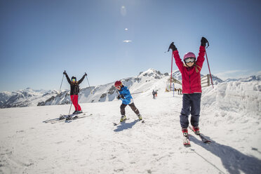 Full length of family enjoying while skiing against clear sky - MASF02463