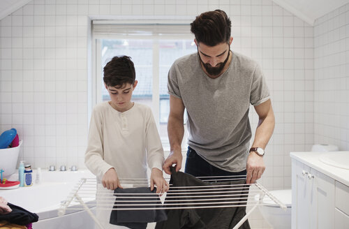 Father and son drying clothes on rack at home - MASF02466
