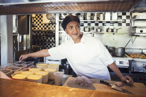 Female chef cooking while looking away at restaurant kitchen - MASF02469
