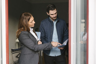 Female realtor assisting man while pointing at brochure by window - MASF02496