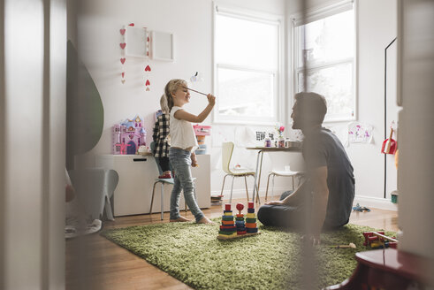 Father looking at daughters playing with toy in playroom at home - MASF02499