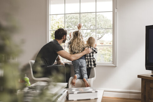 Father with daughters looking through window at home - MASF02502
