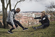 Full length of couple in sportswear exercising on hill - MASF02505