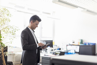 Successful businessman standing in office, using digital tablet - DIGF03892
