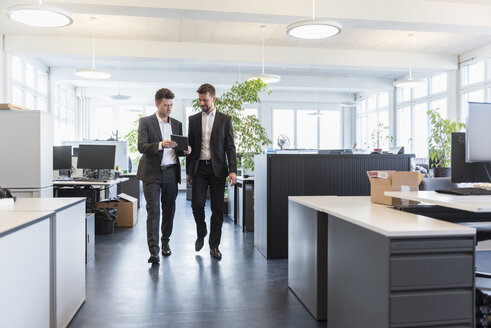 Two businessmen walking in office, using digital tablet, talking - DIGF03895