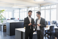 Two businessmen standing in office, discussing solutions, using digital tablet - DIGF03898
