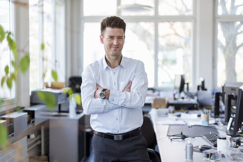 Portrait of a successful businessman standing in office with arms crossed - DIGF03904