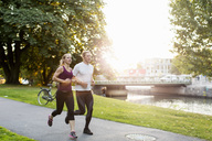 Couple jogging on footpath at park during sunrise - MASF02509