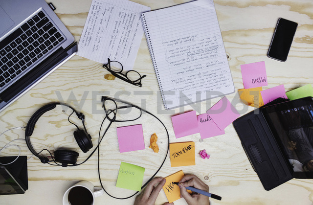 Cropped image of young woman writing in adhesive note at wooden desk - MASF02521