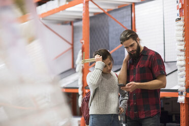 Couple using smart phone while standing in hardware store - MASF02524