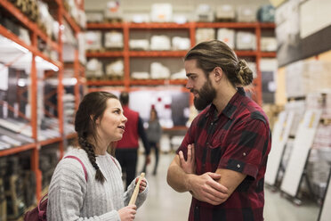 Couple discussing while standing in hardware store - MASF02527