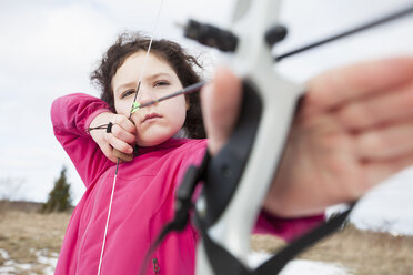 Determined girl practicing archery on field - MASF02530